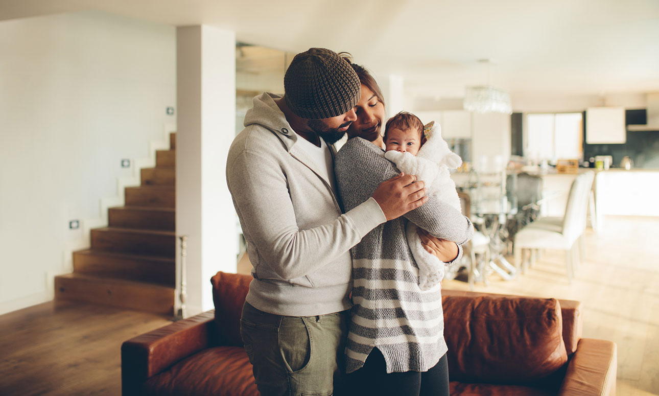 New parents playing with baby in living room
