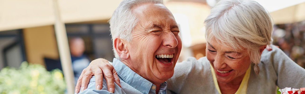 Elderly man and woman laughing