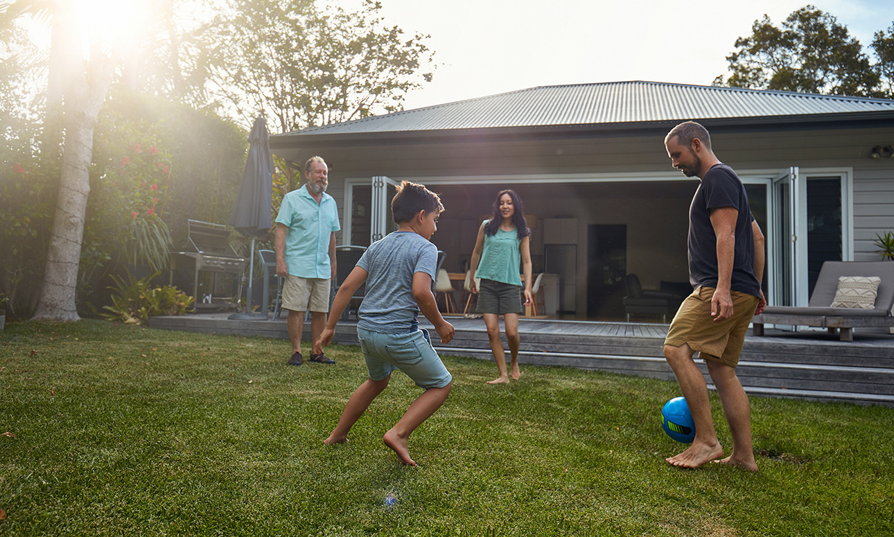 Family playing soccer in their backyard