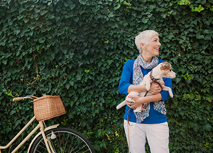 Older woman holding small dog standing next to bike