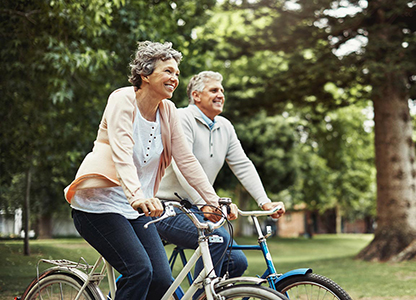 Older couple riding bikes through the park